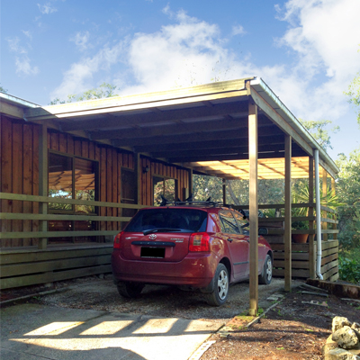 An Attached Wooden Carport With A Simple, Flat Roof.
